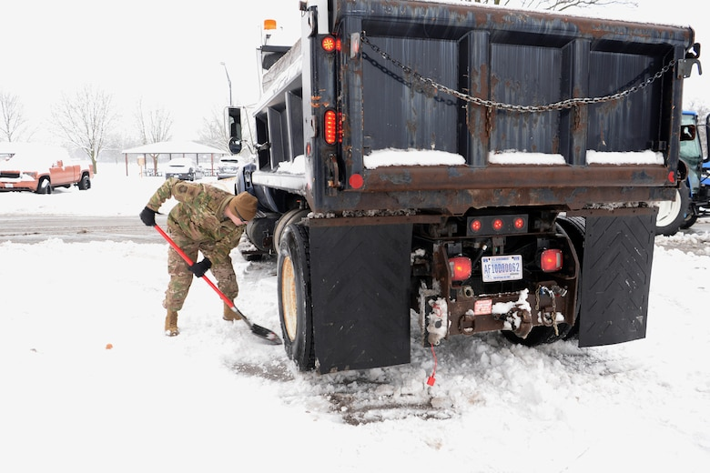 Tech. Sgt. Daniel Brown, 375th Civil Engineer Squadron locksmith NCO in charge, shovels snow away from the tires of a plow truck to give the truck enough traction to continue clearing roads Jan. 12, 2019, at Scott Air Force Base, Illinois. The initial road clearing process takes about three hours but must be continued for as long as the snow is falling to ensure motorists stay safe.