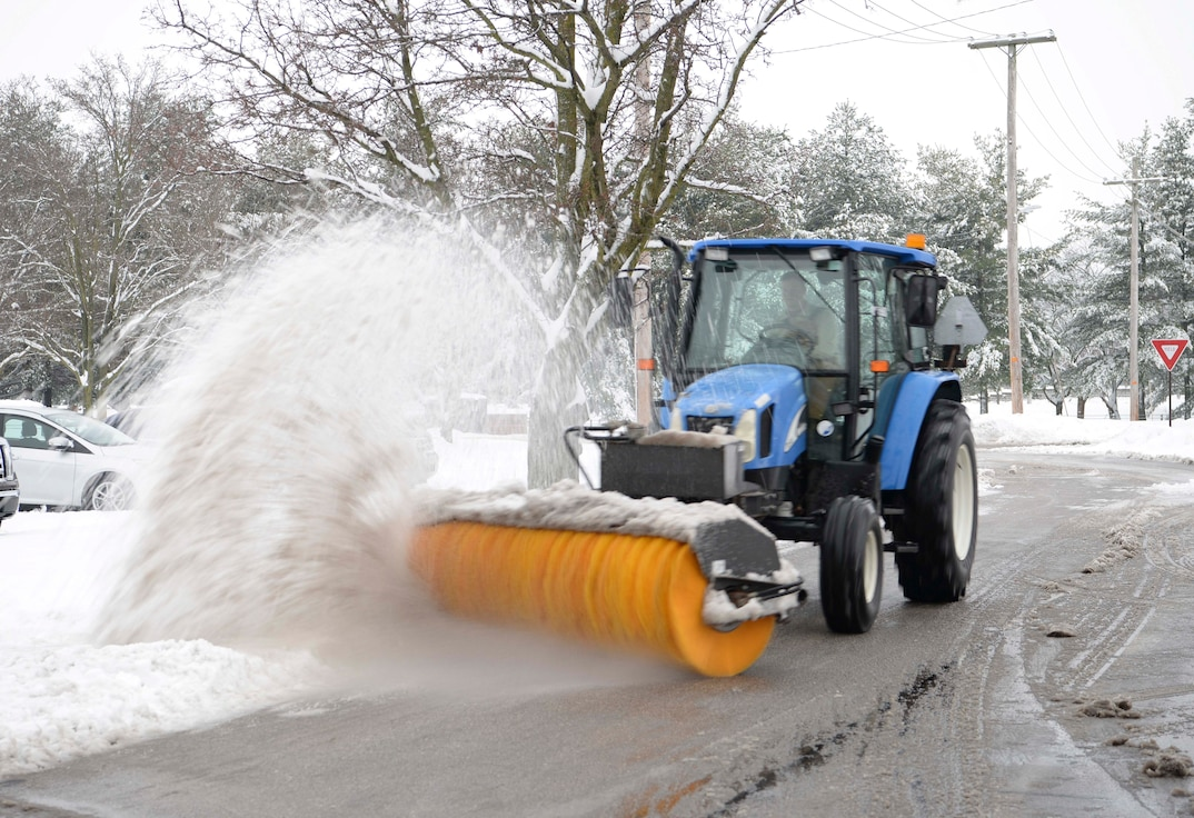 Senior Airman Caleb Lyons, 375th Civil Engineer Squadron water and fuels system maintenance journeyman, uses a tractor and broom to clear snow off the streets Jan. 12, 2019, after heavy snowfall hit Scott Air Force Base, Illinois. Each shift requires about 20 people to aid in the process of clearing the roads.
