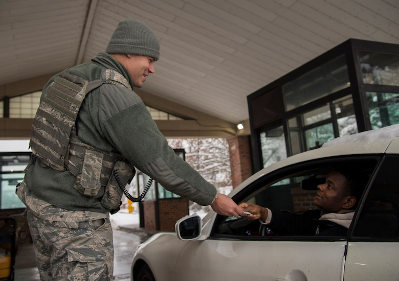 Senior Airman Jay Coil, 375th Security Forces Squadron patrolman, checks an ID card at the Belleville gate Jan. 12, 2019 at Scott Air Force, Ill. Members of the 375th SFS are mission essential personnel and still must ensure the safety and security of the base even during a snow storm.