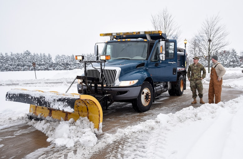 Senior Airman Caleb Lyons, 375th Civil Engineer Squadron water and fuels system maintenance, speaks with Staff Sgt. Justin Henke, 375th CES electrical systems journeyman about clearing the roads  Jan. 12, 2019, after heavy snowfall hit Scott Air Force Base, Illinois. The initial road clearing process takes about three hours but must be continued for as long as the snow is falling to ensure people stay safe.