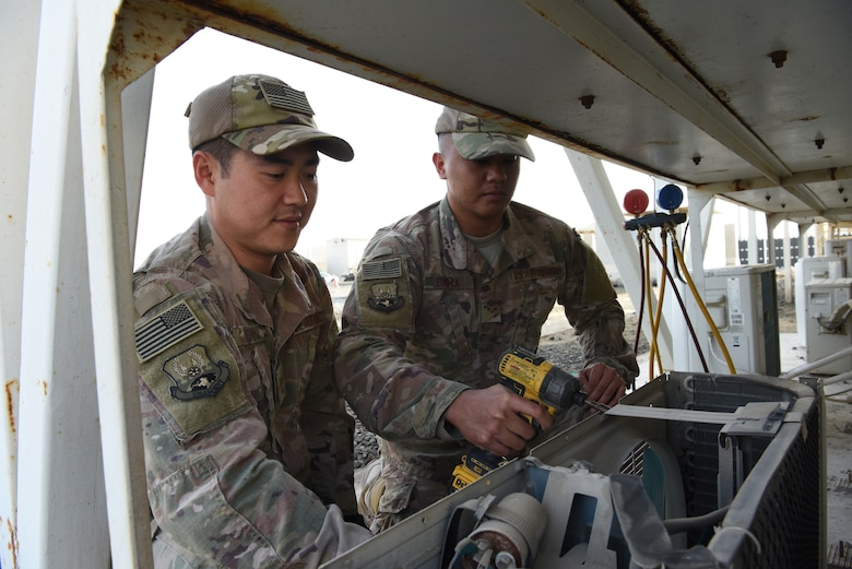 624th Civil Engineer Squadron Reservists Staff Sgt. Roy Shin, 380th Expeditionary Civil Engineer Squadron heating, ventilation, and air conditioning technician, and Senior Airman Elo Badua, 380th ECES HVAC technician, performs maintenance on an air conditioning unit, Jan. 10, 2019 at Al Dhafra Air Base, United Arab Emirates.