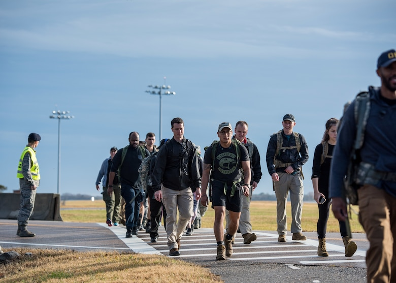 Members of the 633rd Security Forces Squadron, Air Force Office of Special Investigation and Naval Criminal Investigative Services conduct a ruck march in memory of joint patrol team, Hustler 6, at Joint Base Langley-Eustis, Virginia, Dec. 21, 2018.