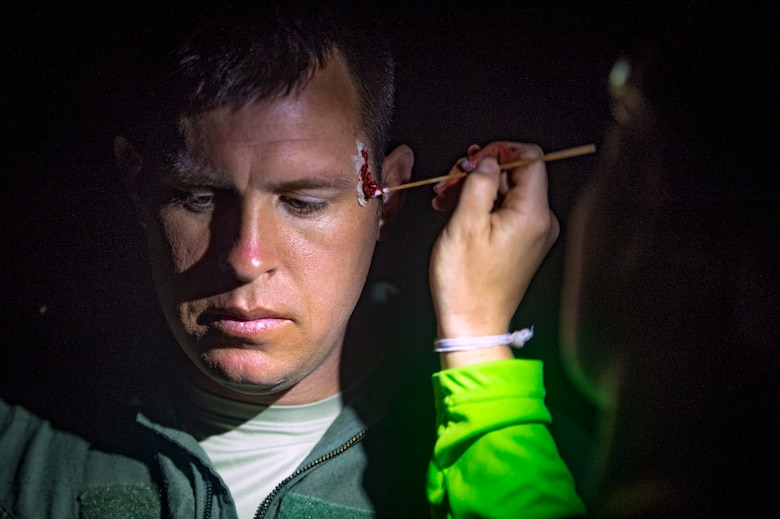 An independent duty medical technician from the 38th Rescue Squadron (RQS) paints simulated wounds onto Tech. Sgt. Levi Wood, 347th Operations Support Squadron NCO in charge of survival evasion resistance and escape (SERE) training, during a personnel recovery scenario as part of pre-deployment 'spin-up' training, Dec. 15, 2018, at Avon Park Air Force Range, Fla. During this pre-deployment 'spin-up' training, Moody's 347th Rescue Group tested and maximized their combat search and rescue (CSAR) and personnel recovery capabilities. Under normal circumstances, the HH-60G Pave Hawk helicopter crews and maintainers deploy from Moody and integrate with Guardian Angel teams from different bases. This time, Moody's 38th RQS and 41st RQS's will deploy together and utilized this exercise to improve their mission readiness and cohesion before their departure. (U.S. Air Force photo by Senior Airman Greg Nash)