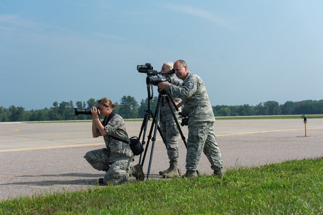 Tech. Sgt. Mary Greenwood, Airman 1st Class Madison Knabe, and Master Sgt. Paul Gorman, all public affairs Airmen with the 115th Fighter Wing, Truax Field, Wis., take photos of aircraft at Volk Field Air National Guard Base during Exercise Northern Lightning 18-2, Aug. 17, 2018. Volk field provides a year-round integrated training environment, which includes airspace, facilities, and equipment, for units to enhance their combat capabilities and readiness.(U.S. Air National Guard photo by Airman 1st Class Cameron Lewis)