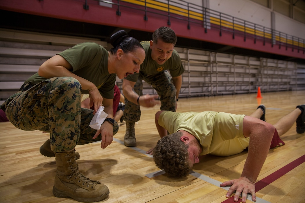 Gunnery Sgt. Kassandra Blade (left), the logistics systems coordinations chief with Headquarters Battalion, Marine Forces Reserve, and Sgt. Brandon Amarahale (center), a personnel clerk with Installation Personnel Administration Center, HQBN, MARFORRES, encourages a member of the Loyola University New Orleans baseball team during a workout session at Loyola University New Orleans, Jan. 12, 2019. Blade, a former drill instructor, brought her experience to help lead a workout that was physically challenging to the participants but also focused on teamwork and leadership. The workout session was comprised of four events; incentive training, shamrock drill, Marine Corps Martial Arts Program demonstrations and casualty evacuation drills. (U.S. Marine Corps photo by Cpl. Niles Lee)