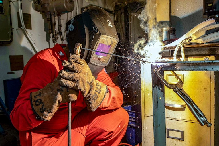 A sailor welds some metal together.