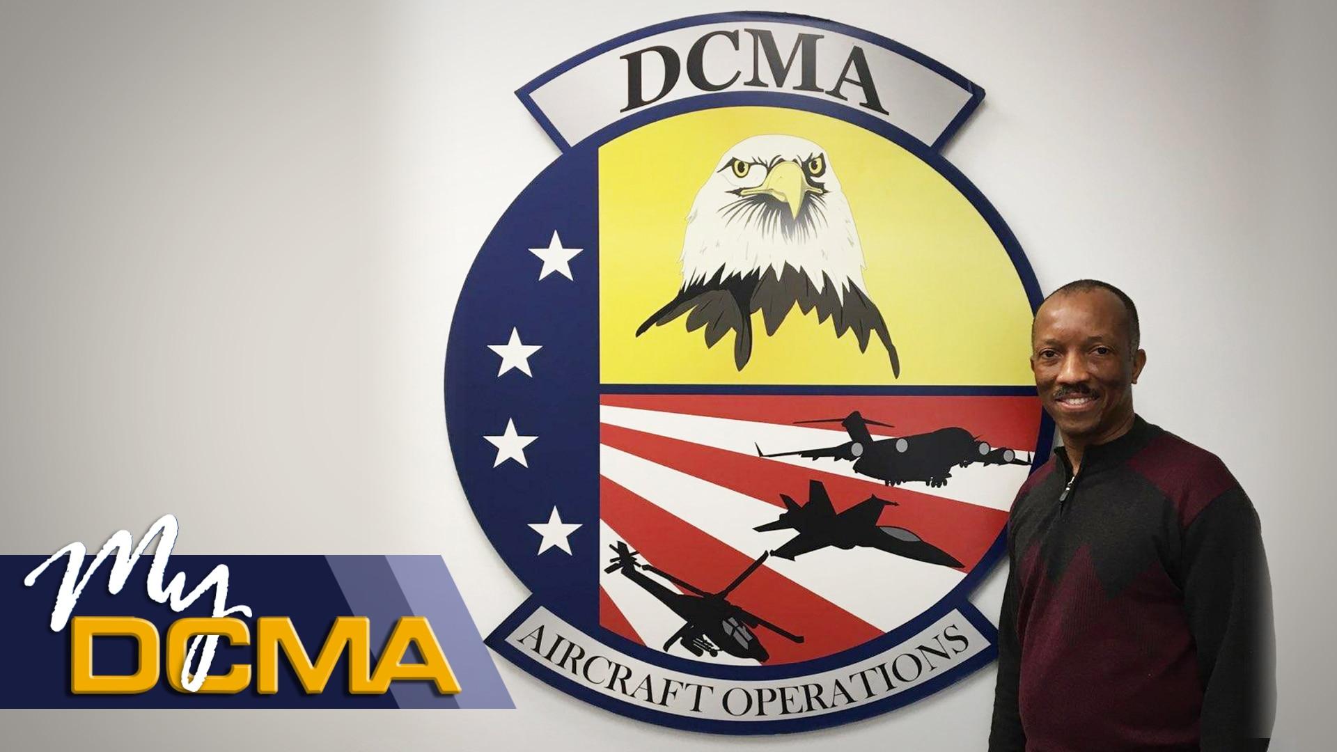 Man stands beside a DCMA sign.