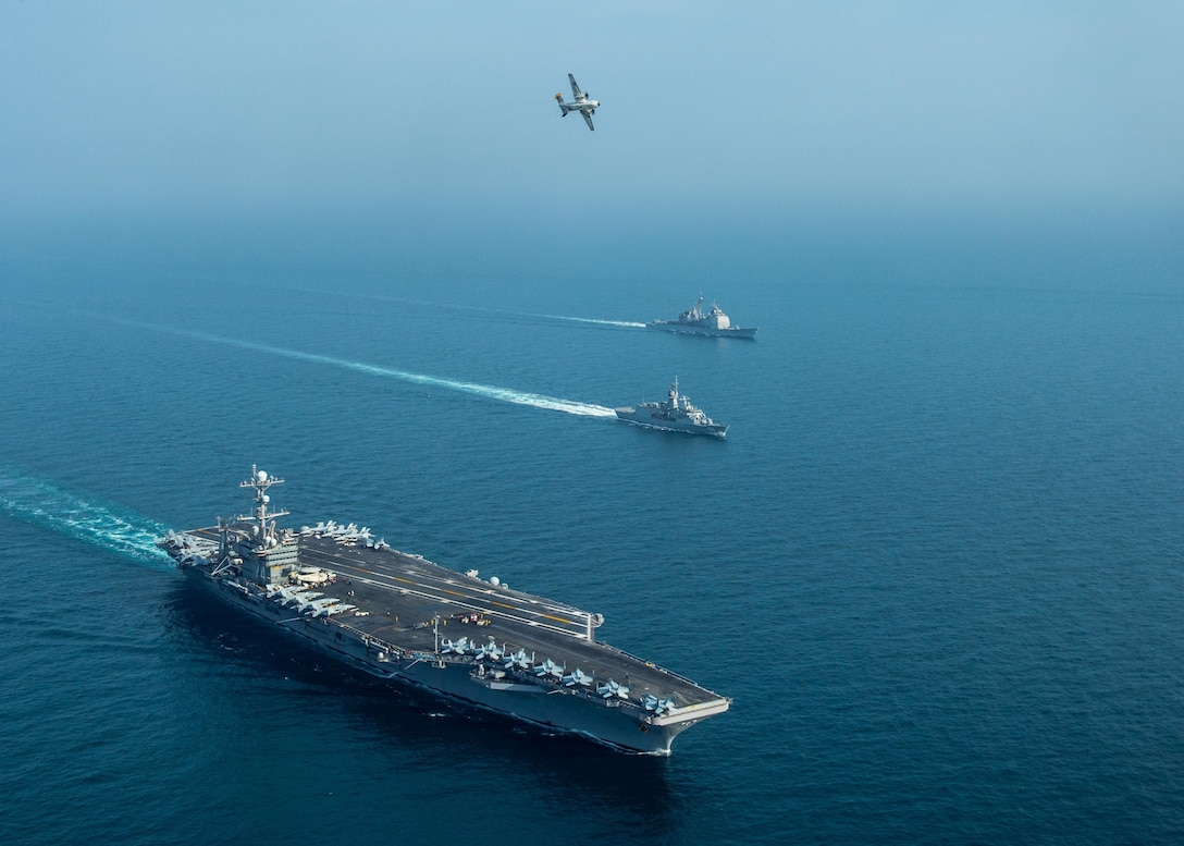 From left to right, the aircraft carrier USS John C. Stennis (CVN 74), the Royal Australian Navy frigate HMAS Ballarat (FFH 155) and the guided-missile cruiser USS Mobile Bay (CG 53) sail in formation as a C-2A Greyhound, assigned to Fleet Logistics Combat Support Squadron (VRC) 30, detachment 4, conducts a flyover in the Arabian Gulf, Jan. 16, 2019, during exercise Intrepid Sentinel. Intrepid Sentinel brings together the John C. Stennis Strike Group, France's Marine Nationale, United Kingdom's Royal Navy and the Royal Australian Navy for a multinational exercise designed to enhance war fighting readiness and interoperability between allies and partners. The John C. Stennis Strike Group is deployed to the U.S. 5th Fleet area of operations in support of naval operations to ensure maritime stability and security in the Central Region, connecting the Mediterranean and the Pacific through the western Indian Ocean and three strategic choke points.  (U.S. Navy photo by Mass Communication Specialist 3rd Class Jake Greenberg)