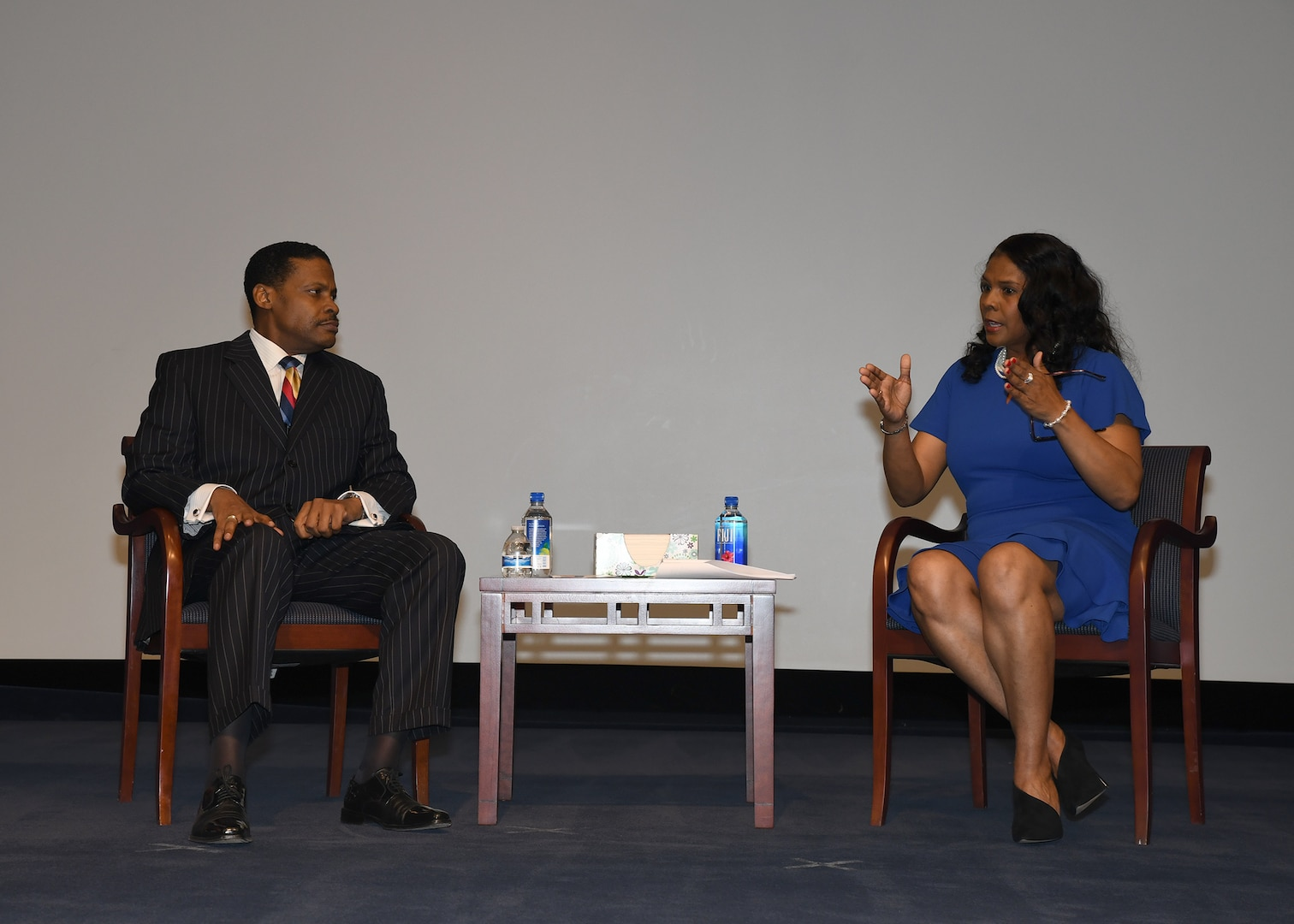 Man, woman seated on stage mid-discussion