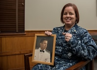 U.S. Navy Commander Kerry Beasley, poses for a photo with a portrait of her father, Maj. Wayne Brown II, while holding the two 497th Tactical Fighter Squadron rings at Joint Base Langley-Eustis, Virginia, Jan. 9, 2019.