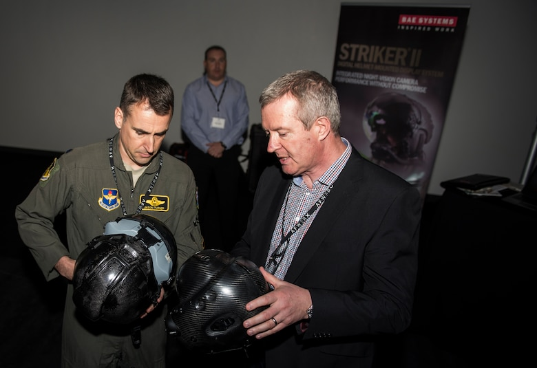 An Airman and an attendee of the AFWERX Helmet Challenge discuss new helmets at the Enclave Las Vegas, Nev., November 14, 2018. The final goal of the challenge is to enhance aircrew performance, aircrew safety and aircrew satisfaction. (U.S. Air Force photo by Airman 1st Class Bryan T. Guthrie)