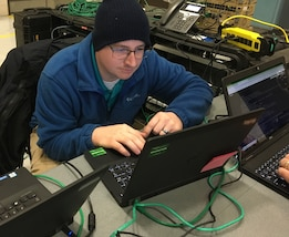 "Colin Walton, a network engineer at Joint Task Force Civil Support (JTF-CS), participates in the command's first tactical satellite (TACSAT) communication exercise (COMMEX) of the new year January 15, 2019 at Felker Army Airfield on Fort Eustis in preparation for exercise Sudden Response 19 (SR19) held on January 24-30. SR19, held at Fort Bragg, NC this year, is a command-led exercise that tests JTF-CS and Defense Chemical, Biological, Radiological and Nuclear (CBRN) Response Force (DCRF) capabilities to response to a catastrophic CBRN event. When directed, JTF-CS is ready to respond in 24 hours to provide command and control of 5,200 federal military forces located at more than 36 locations throughout the nation in support of civil authority response operations to save lives, prevent further injury and provide critical support to enable community recovery. (Official DoD photo by David ""Rick"" George/released)"