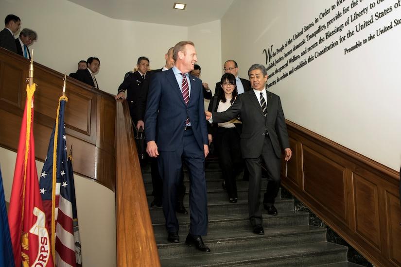 Acting Defense Secretary Patrick M. Shanahan walks down the stairs followed by a group of people.