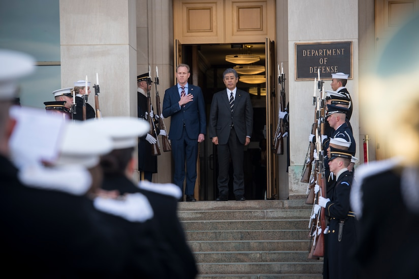 Acting Defense Secretary Patrick M. Shanahan  stands at the top of steps with a Japanese official.