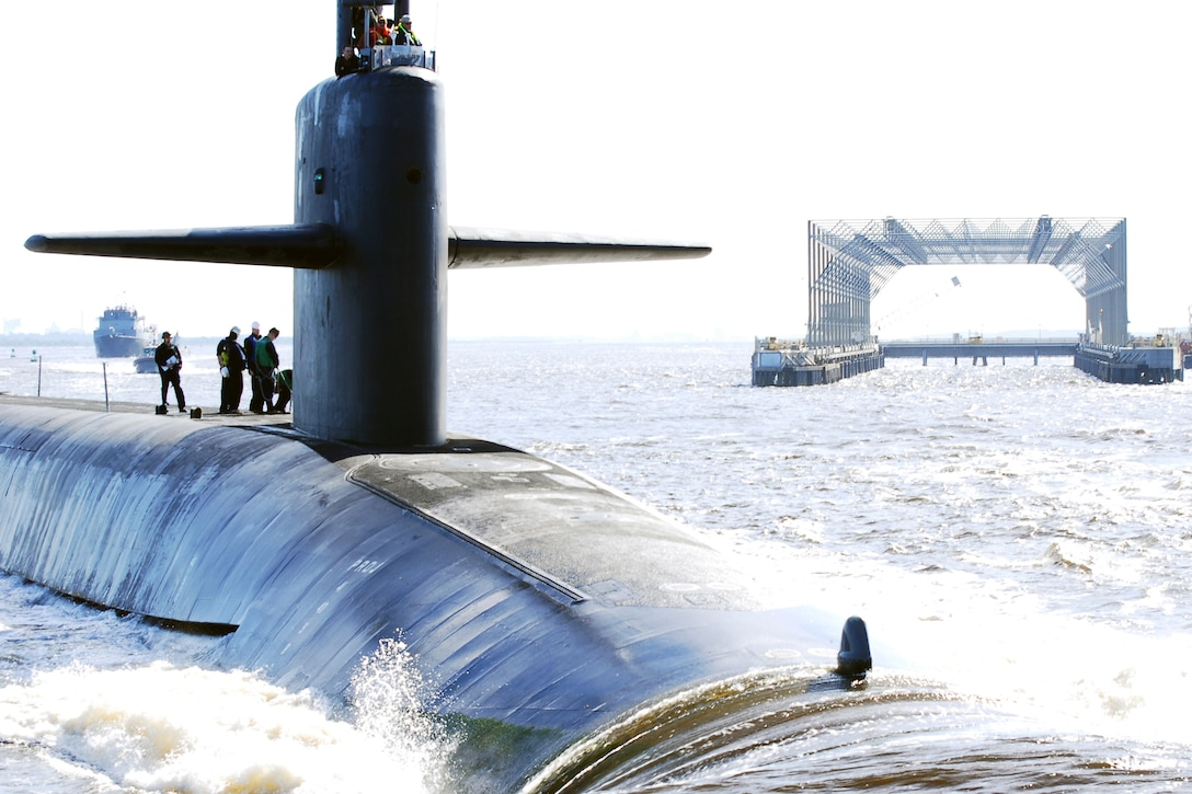 Six submariners stand atop of a submarine as it returns to its home port.