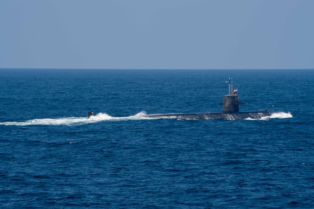 A submarine pushes through the water partially submerged.