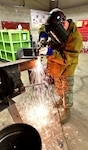 U.S. Air Force Master Sgt. James Childs, 173rd Fighter Wing vehicle maintenance shop, releases a cascade of sparks with a cutting torch during fabrication of a support bracket for a roll-over snow plow, Jan. 14, 2019. If a part is unavailable, then the mechanics at the 173rd Fighter Wing vehicle maintenance shop at Kingsley Field in Klamath Falls, Oregon fabricate it themselves in order to quickly return the vehicle to operation.