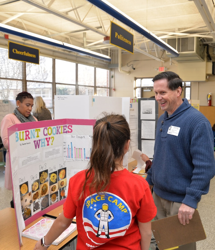 Russ Dunford, who manages strategic plans and integration at Huntsville Center, interviews sixth-grader Hannah Austin during Monte Sano Elementary School's science fair for sixth-grade honor students Jan. 10, 2019, in Huntsville, Alabama.