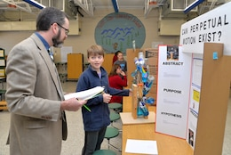 Tom O. Meier, director of Huntsville Center's Management Review Office, interviews a student during Monte Sano Elementary School's science fair for sixth-grade honor students Jan. 10, 2019, in Huntsville, Alabama.