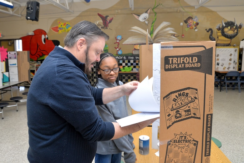 Mark Reed, contract specialist and former science teacher, reviews Marteka Russell's science project on how salinity affects the buoyancy of an egg. Russell was one of 27 sixth-grade honor students to participate in the science fair Jan. 10, 2019, at the Monte Sano Elementary School in Huntsville, Alabama.