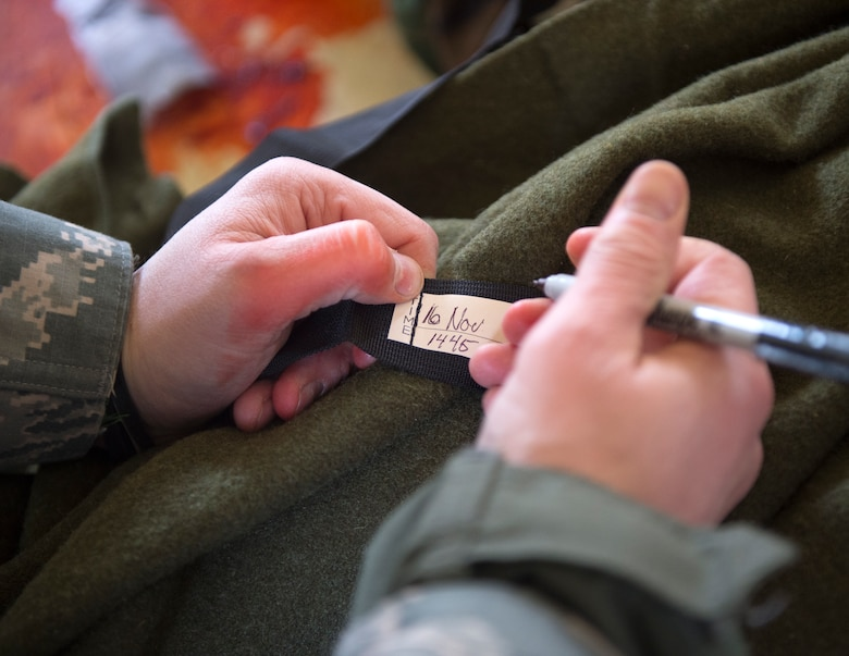 A member from the 133rd Airlift Wing writes the time and date in which the tourniquet was placed onto the simulated patient at the Arden Hills Army Training Site in Arden Hills, Minn., Nov. 16, 2018.