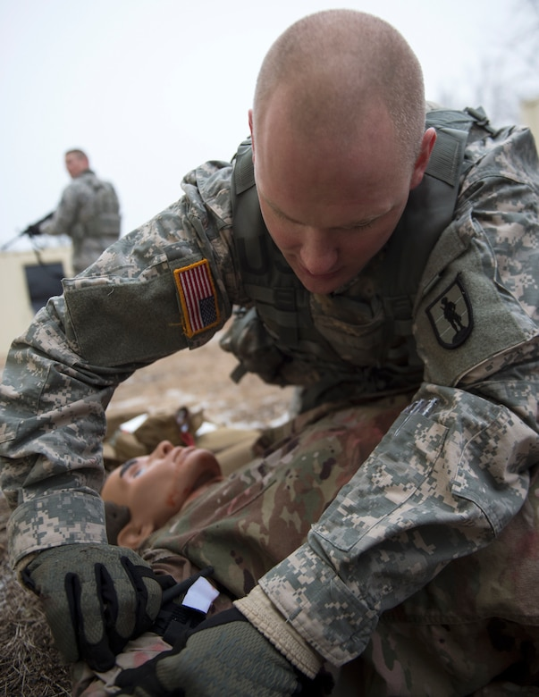 U.S. Army Staff Sgt. Ryan Kelly, 2nd Battalion (Modular Training), 175th Regiment (Regional Training Institute), places a tourniquet onto a simulated patient's arm at the Arden Hills Army Training Site in Arden Hills, Minn., Nov. 16, 2018.