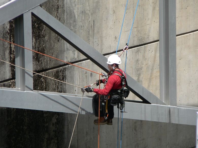 A Dam Safety Program inspector dangles from the face of a Willamette Valley dam as he assesses the condition of spillway gates, June 6, 2009. The dam safety assessment concluded gates could fail to open or could stick, which could affect how the dams released water. In 2010, the District began rehabilitating the gates.