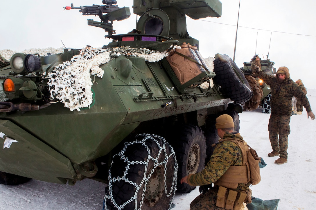 Marines and sailors install snow chains on the tires of a light armored vehicle.