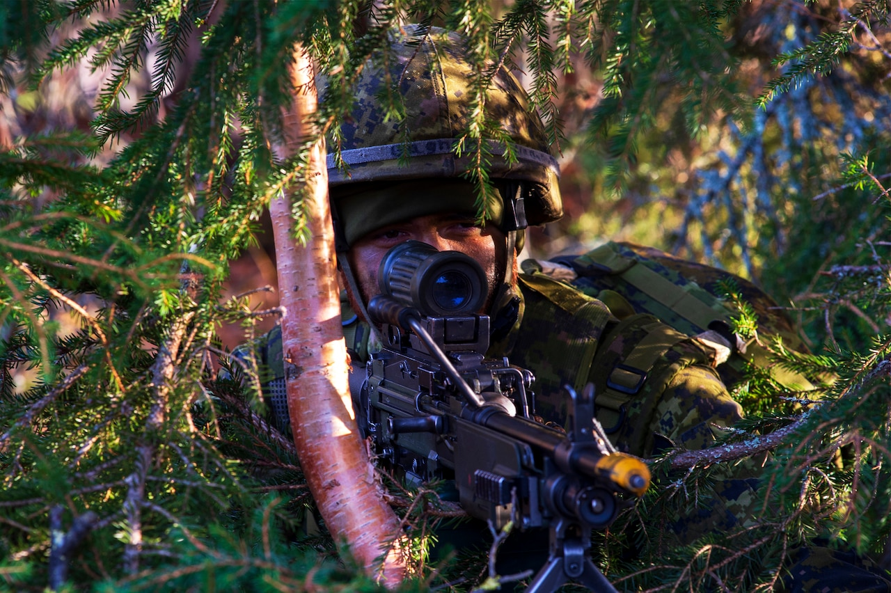 A soldier in camouflage aims his rifle through some foliage.