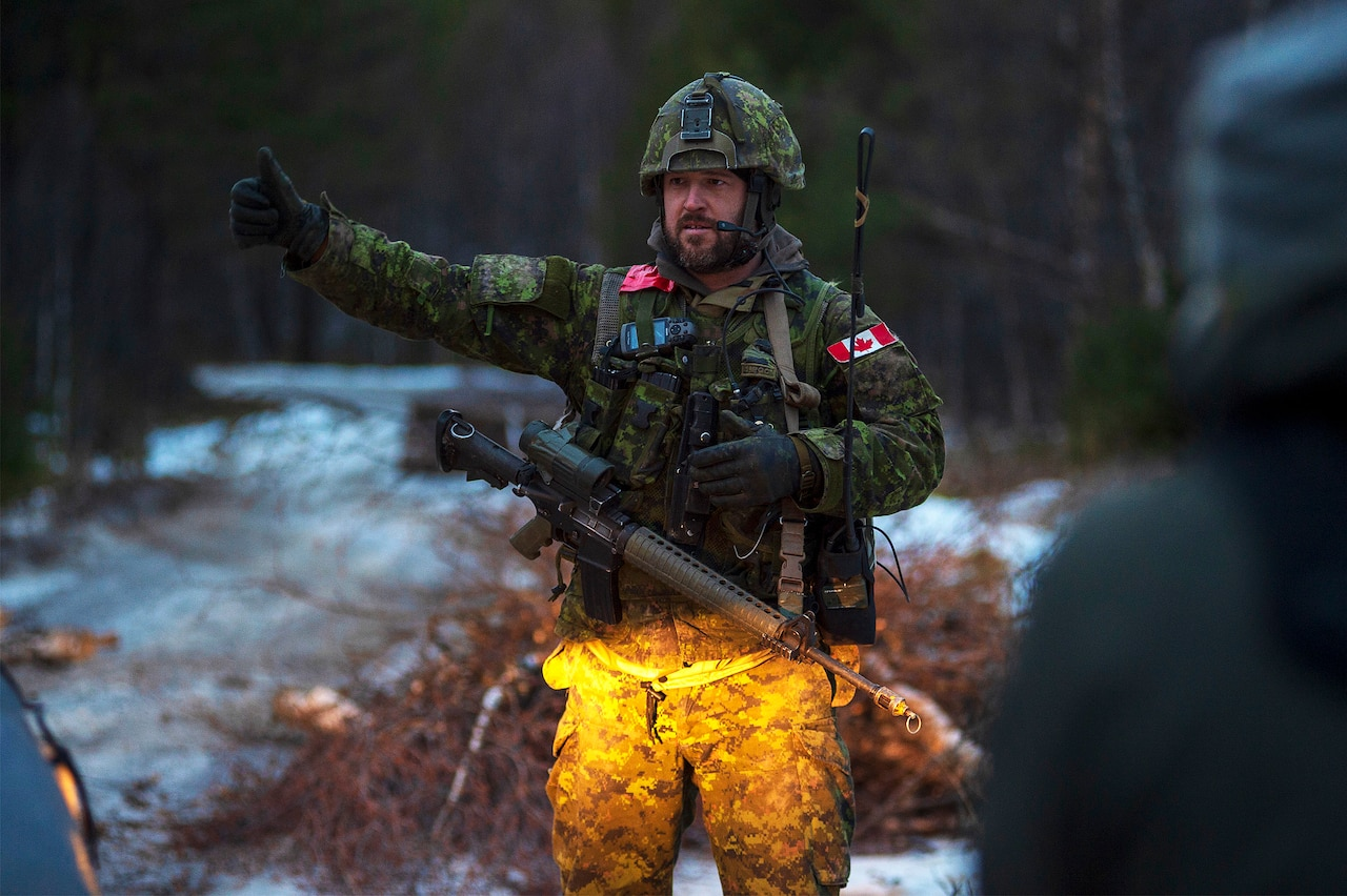 A soldier in camouflage holds a thumbs up.