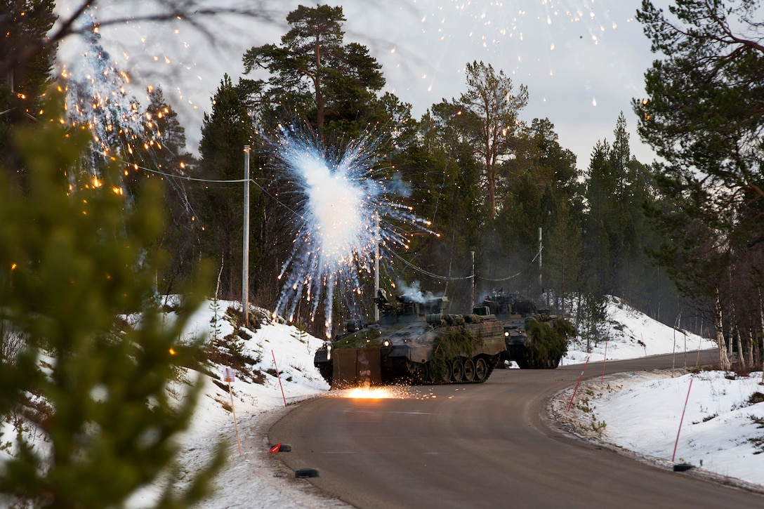 A tank round simulator explodes near two infantry combat vehicles.
