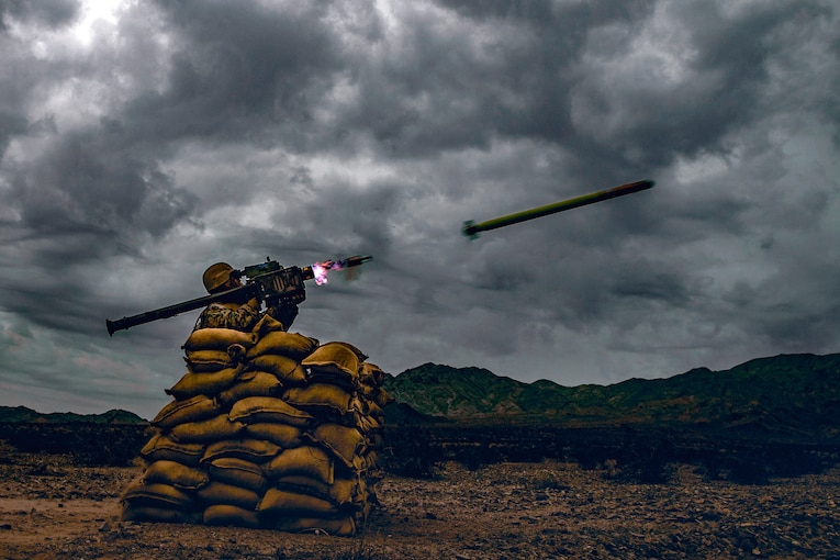 A Marine fires a missile from behind sandbag cover.