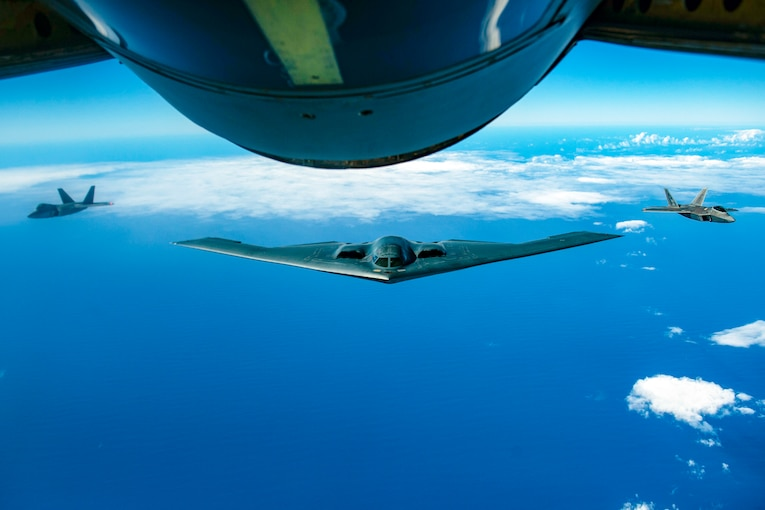 A B-2 bomber flies over the ocean with two other planes at its side.