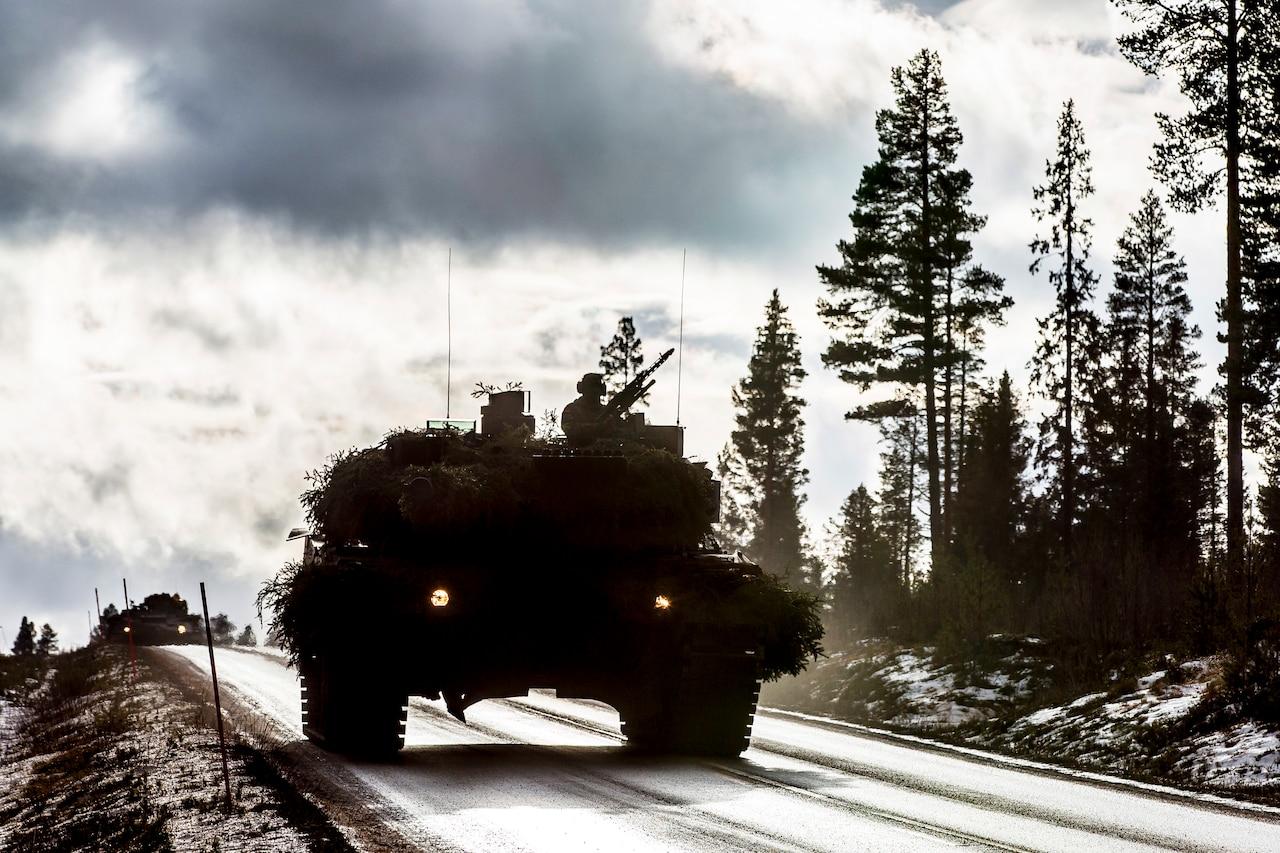 A tank drives down a snowy road.