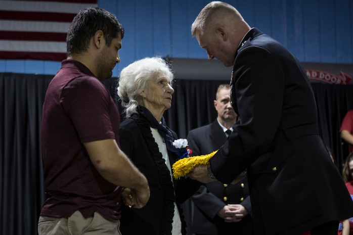 Maj. Gen. Bradley S. James, commander of Marine Forces Reserve and Marine Forces North, presents the Medal of Honor flag to Sgt. Alfredo Cantu Gonzalez's mother, Dolia Gonzalez, at the Freddy Gonzalez Elementary school in Edinburg, Texas, Jan. 14, 2019. Gonzalez served two tours in the Vietnam War and was killed on Feb. 4, 1968. (U.S. Marine Corps photo by Cpl. Tessa D. Watts)