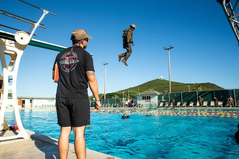 A man watches a Marine dive into a swimming pool.