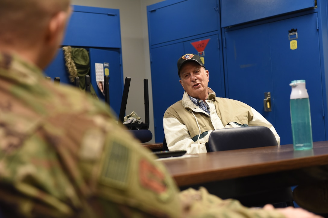 """Retired Chief Master Sgt. Edward """"Buck"""" Boyd sits at a table in mid conversation."""