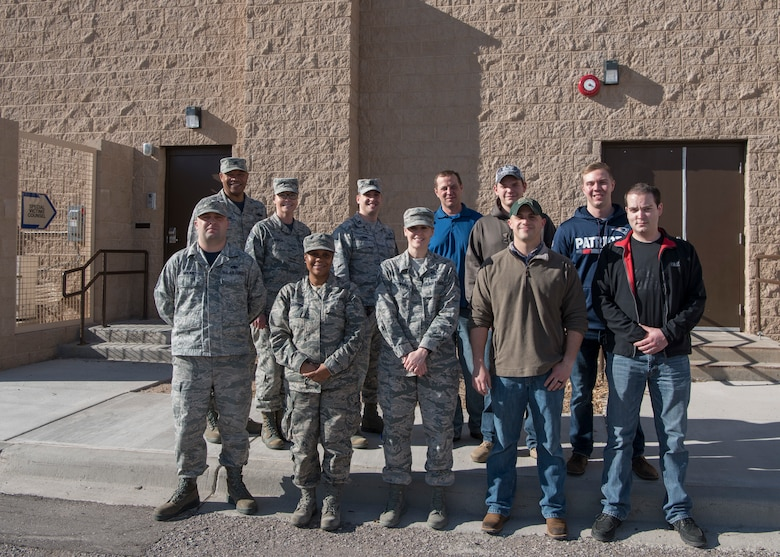 Airmen pose for a group photo outside of building 788, Jan. 11, 2019, on Holloman Air Force Base, N.M. Col. Brian Patterson, 49th Wing vice commander, and Chief Master Sgt. Sarah Esparza, 49th Wing command chief, celebrated the opening of the Special Victims' Counsel's new office. (U.S. Air Force photo by Airman Autumn Vogt)
