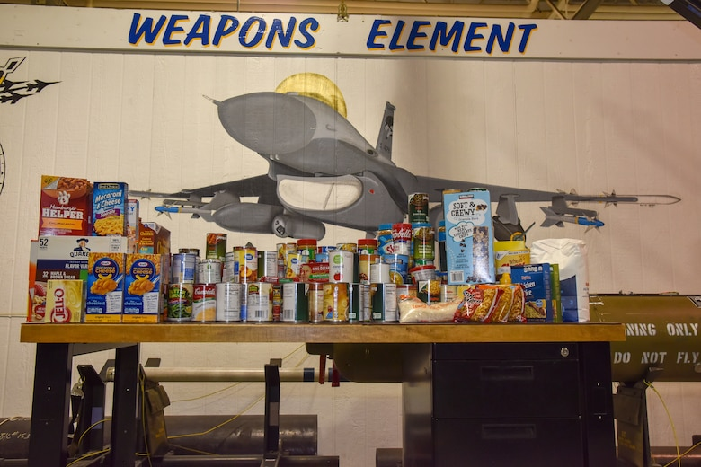 The 114th Aircraft Maintenance Squadron Weapons Element gave back to the hungry in South Dakota by donating canned goods they collected in their shop during the January unit training assembly and the money raised during a taco feed fundraiser in December to Feeding South Dakota.
