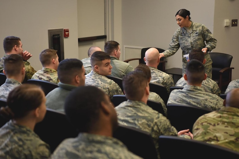 Staff Sgt. Symphony Leyk, 5th Force Support Squadron Airman Leadership School Instructor, hands out envelopes to class leaders, at Minot Air Force Base, N.D., Jan. 15, 2019. Airman leadership school class size may vary, but typically have 64 students broken down into four flights. (U.S. Air Force photo by Airman 1st Class Heather Ley)