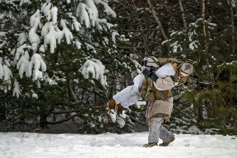 A soldier carries another soldier during training in the snow.
