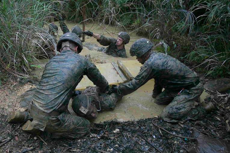 Marines work together to complete an endurance course.