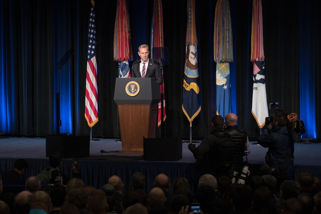 Acting Defense Secretary Patrick M. Shanahan addresses an audiences from a lectern on a stage.