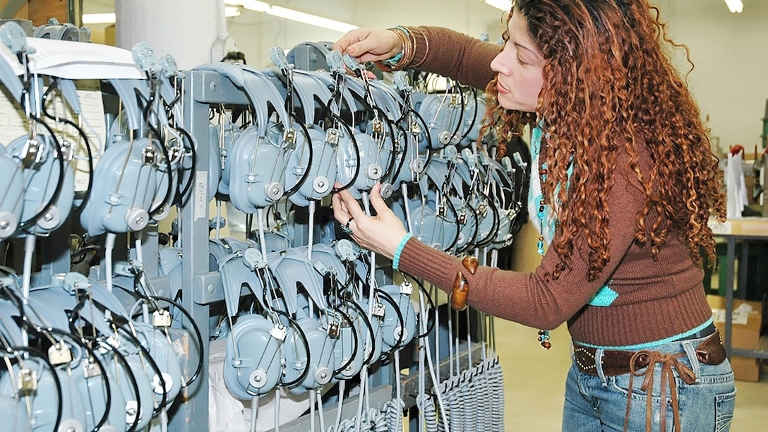 An employee handles finished aviation headsets on a rack