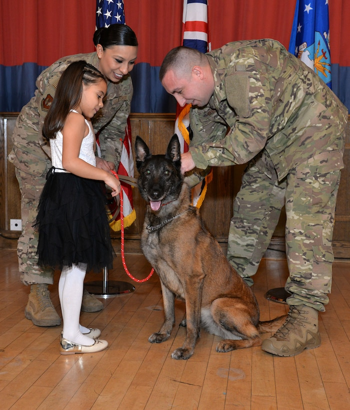 U.S. Air Force Tech. Sgt. Kelly Webster, right, 100th Security Forces Squadron Military Working Dog kennel master, and his wife Staff Sgt. Jacqueline Rosales, 100th SFS response force leader, and daughter Aubrey, put a new red, civilian collar on former MWD Vvonya at her retirement ceremony at RAF Mildenhall, England, Jan. 18, 2019. Webster and his family have adopted Vvonya as she retires after nine years military service. (U.S. Air Force photo by Karen Abeyasekere)