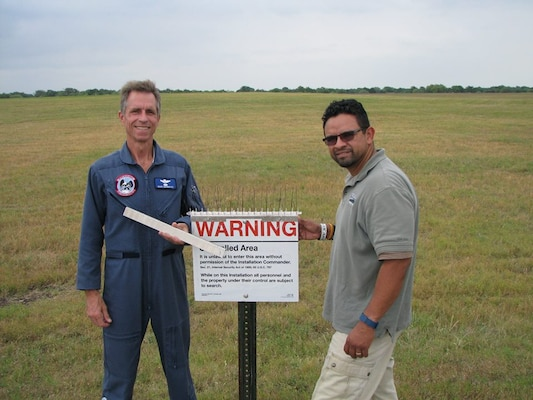 David Bernacki, 12th Training Squadron Introduction to Fighter Fundamentals simulator/academic instructor supervisor, and Mike Pacheco, 12th Flying Training Wing Safety Office wildlife biologist, display Bernacki's patent-pending Anti-Bird Perch Attachment for Signs, or ABPAS, at Joint Base San Antonio-Randolph. The attachment mounts on signs to hold bird spikes used in the Bird Aircraft Strike Hazard program. Bernacki is the Air Education and Training Command winner of the 2019 Air Force Association Lisa S. Disbrow Outstanding Civilian of the Year Award. Courtesy photo.