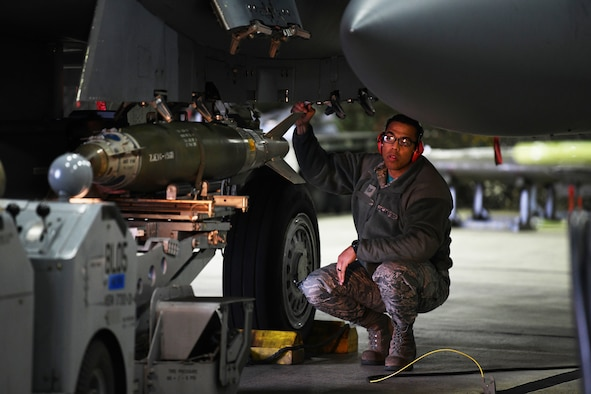 A loading standardization crew member observes the loading of an inert MK-82 ordinance on an F-15E Strike Eagle during a loading competition at Royal Air Force Lakenheath, England, Jan. 18, 2019. The load crew team were judged on their ability to load both an inert MK-82 and a GBU-38 on the aircrafts. (U.S. Air Force photo by Airman 1st Class Shanice Williams-Jones)