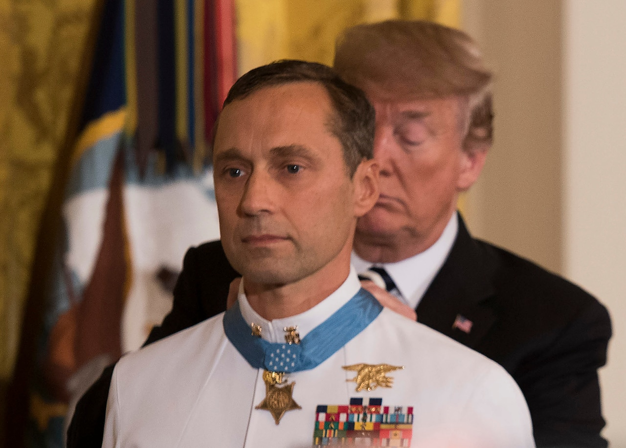 President Trump places the Medal of Honor around a recipient's neck.