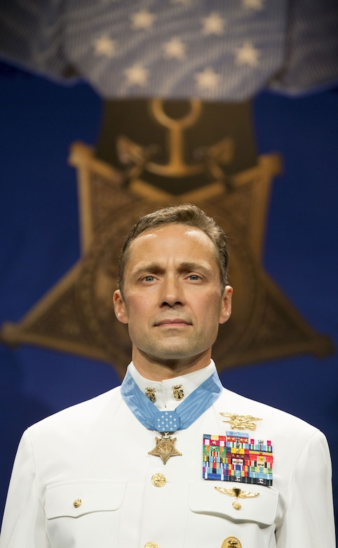 A Navy SEAL wearing the Medal of Honor stands in front of a large picture of the Medal of Honor.