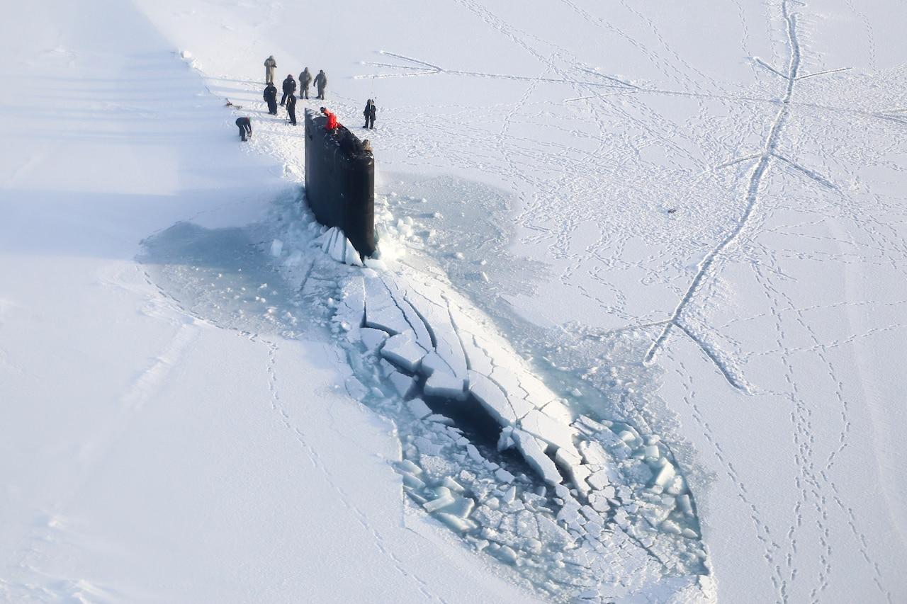 A submarine surfaces through ice.